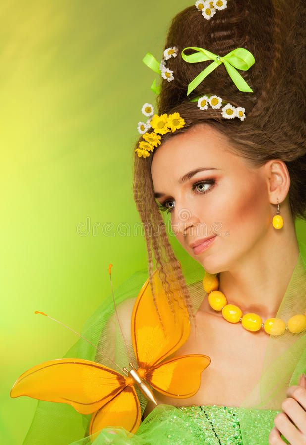 Beauty portrait with big butterfly. Beauty portrait of attractive woman with big yellow butterfly, bows and wild flowers in her hair and dress, with professional royalty free stock photos
