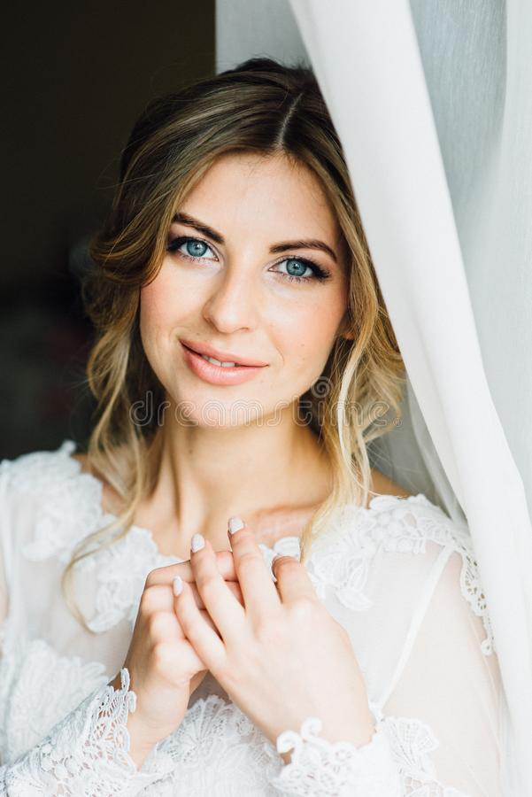 Beauty portrait of bride wearing fashion wedding dress with feathers with luxury delight make-up. And hairstyle, indoor photo. Young attractive Caucasian model stock photography