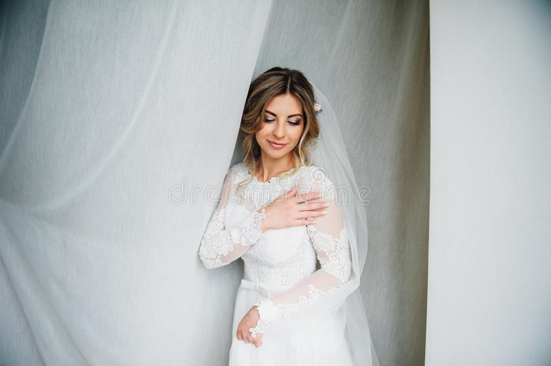 Beauty portrait of bride wearing fashion wedding dress with feathers with luxury delight make-up stock photography