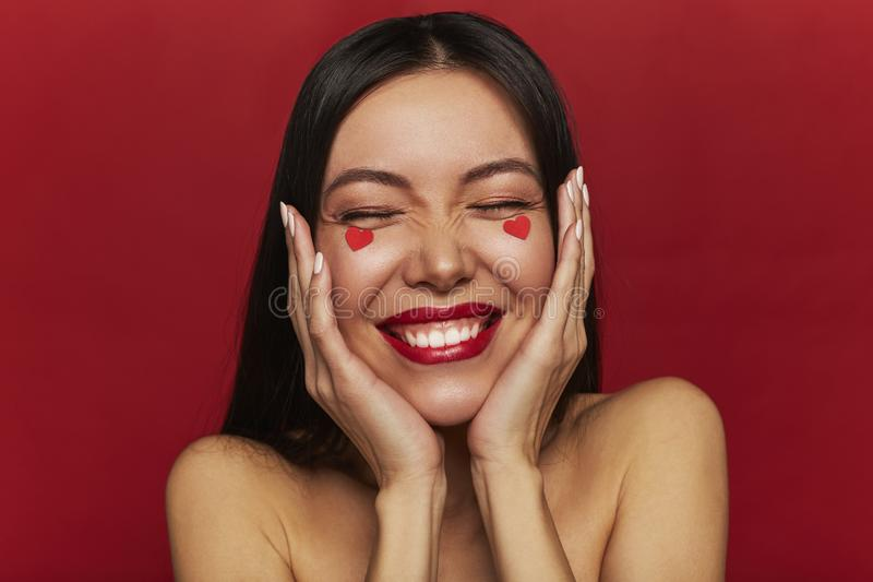 Beauty portrait of brunette happy woman with hearts on her face. Valentine`s Day portrait of attractive smiling woman love make-up royalty free stock image