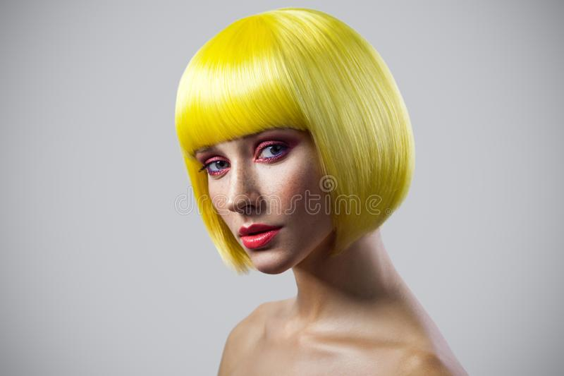 Beauty portrait of calm cute young female model with freckles, red makeup and yellow wig looking at camera with serious face stock photo