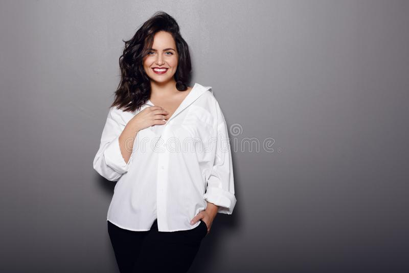 Beauty portrait of cheerful brunette woman, wear in white shirt and black pants, isolated on a grey background. Smiling young woman touching neck and looking at royalty free stock image