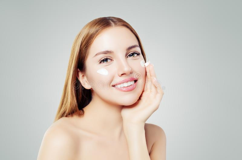 Beauty portrait of cute young woman smiling while applying some facial cream on her cheek.  stock photography