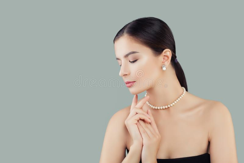 Beauty portrait of elegant model woman in pearls necklace and earrings royalty free stock photo