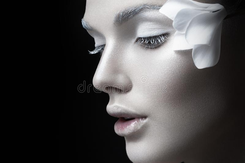 Beauty portrait., girl with white makeup, anf flowers near ear. Concept makeup, cosmetics,  on black background. stock image