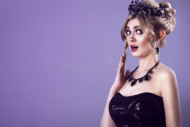 Beauty portrait of gorgeous extremely surprised young blond woman with updo hair and black jewel crown on her head stock image