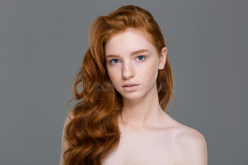 Beauty portrait of gorgeous natural redhead woman with wavy hair. Over grey background royalty free stock photography