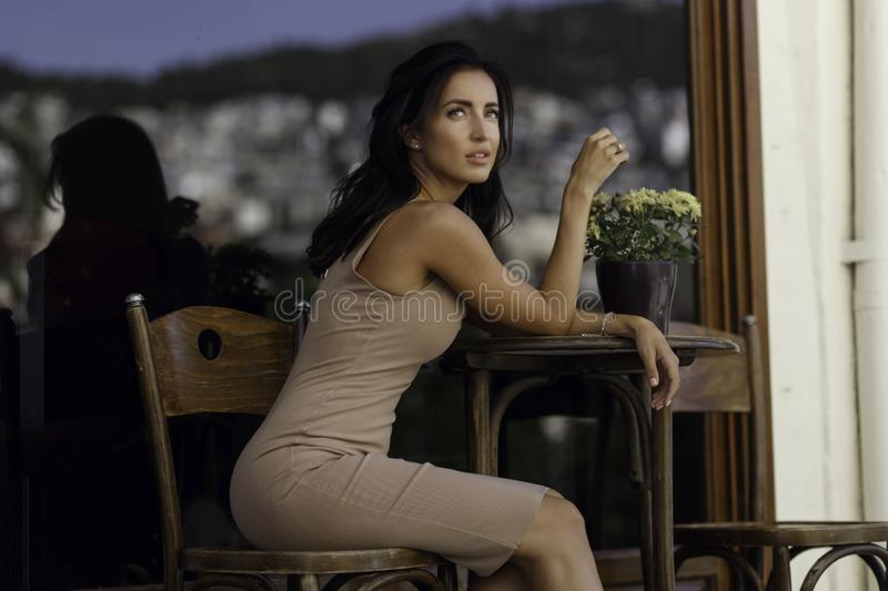 Profile beauty portrait of a graceful brunette young woman, stays at a coffee table, poses alone gorgeous outside. stock photo