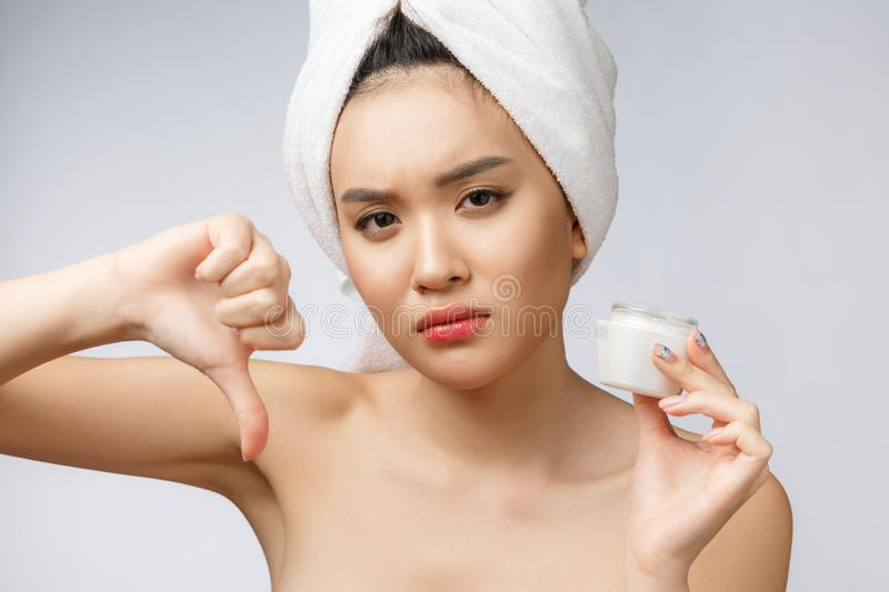 Beauty portrait of half-naked asian woman looking on camera and holding face cream on her palm isolated over white stock photos