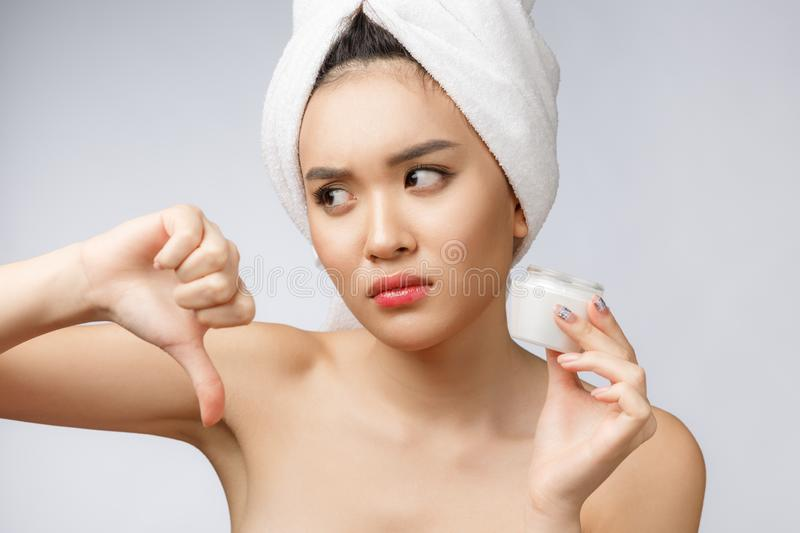 Beauty portrait of half-naked asian woman looking on camera and holding face cream on her palm isolated over white royalty free stock image