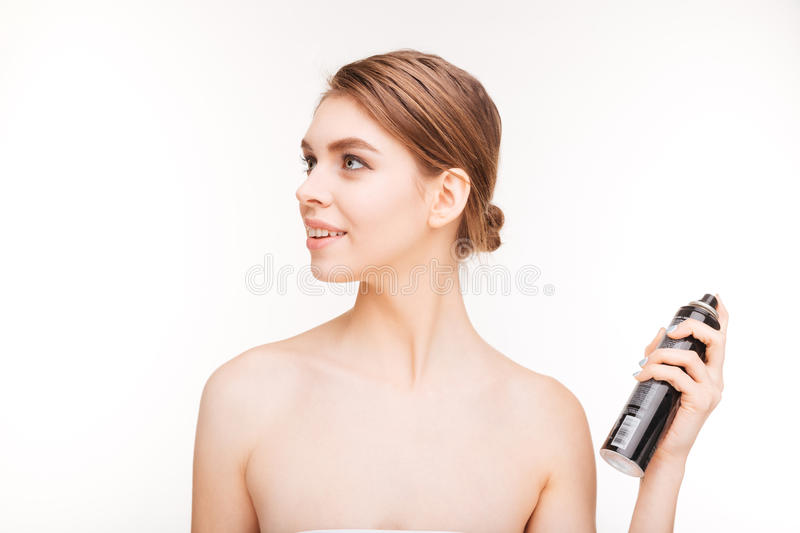 Beauty portrait of happy woman applying hairspray on her hair royalty free stock photo