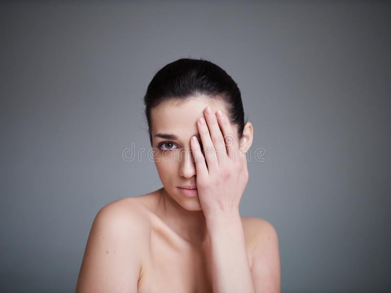 Beauty portrait of healthy female face with natural skin on grey background. Cosmetology concept stock images