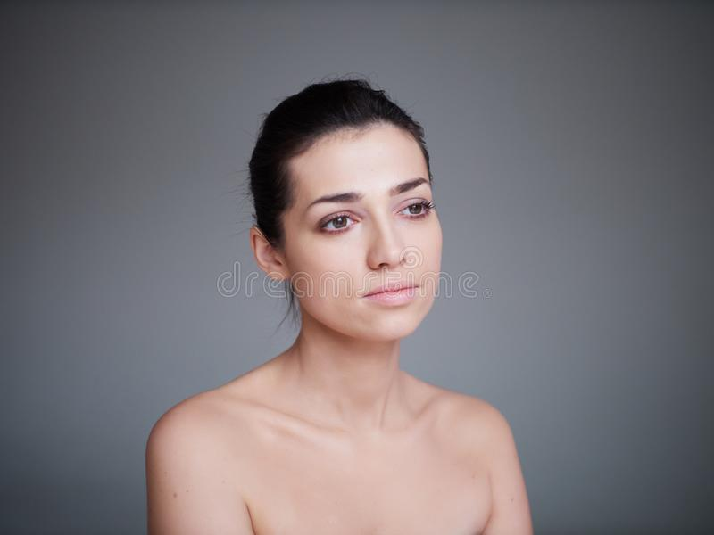 Beauty portrait of healthy female face with natural skin on grey background. Cosmetology concept stock photo