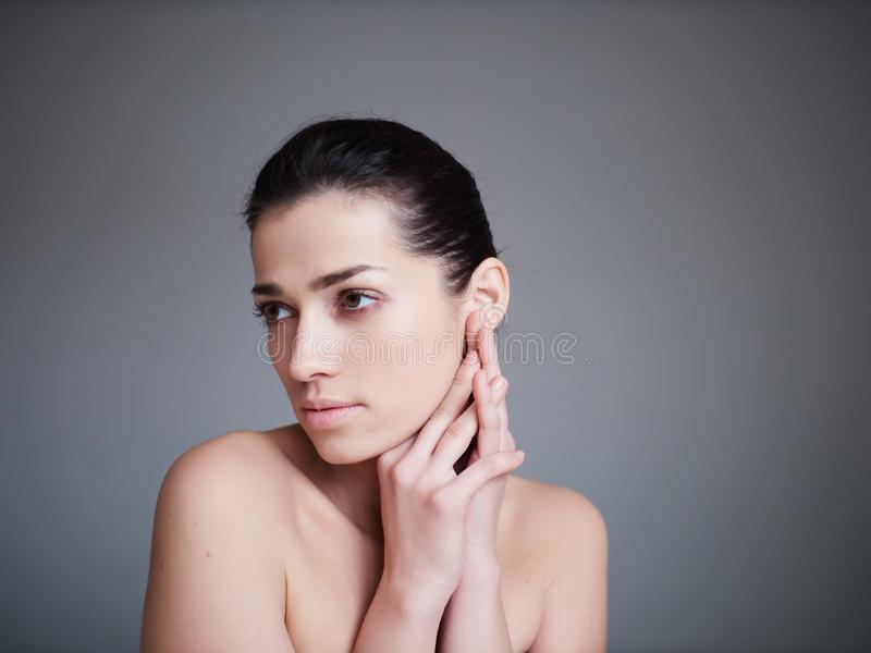 Beauty portrait of healthy female face with natural skin isolated on grey background. Cosmetology concept stock photos