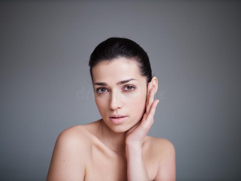 Beauty portrait of healthy female face with natural skin isolated on grey background. Cosmetology concept royalty free stock images