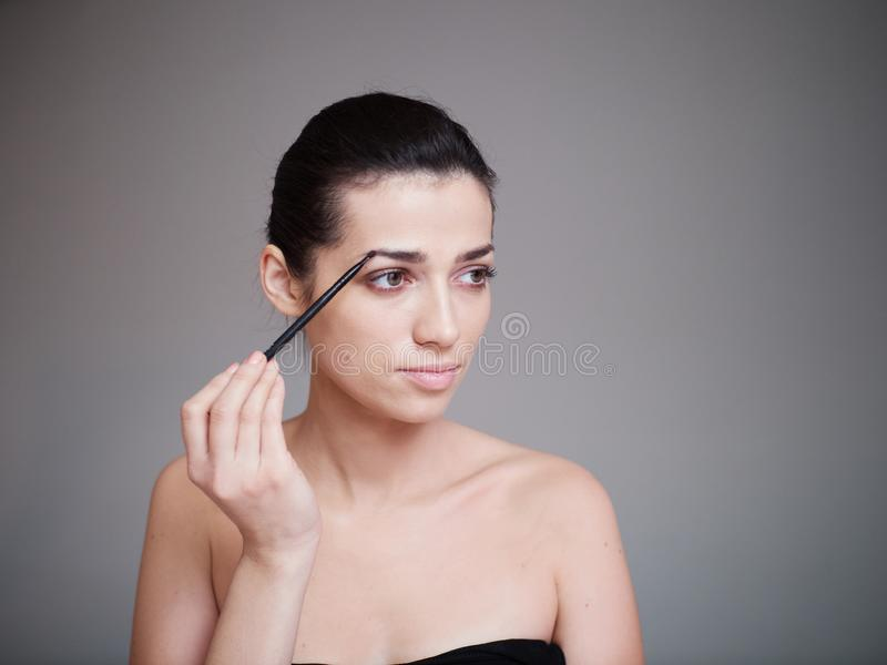 Beauty portrait of healthy female face with natural skin isolated on grey background. Make up concept royalty free stock photo