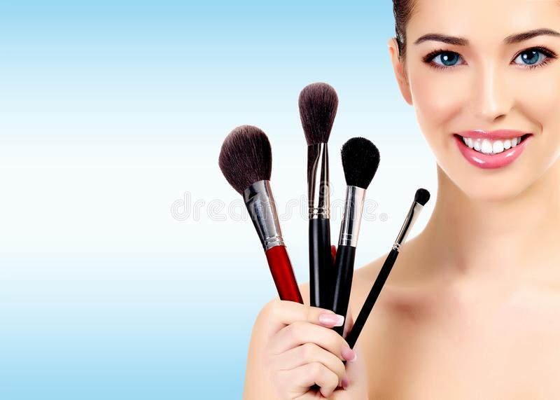 Beauty portrait of lovely beautiful happily smiling woman holding a bunch of make-up brushes against a light blue background stock photos