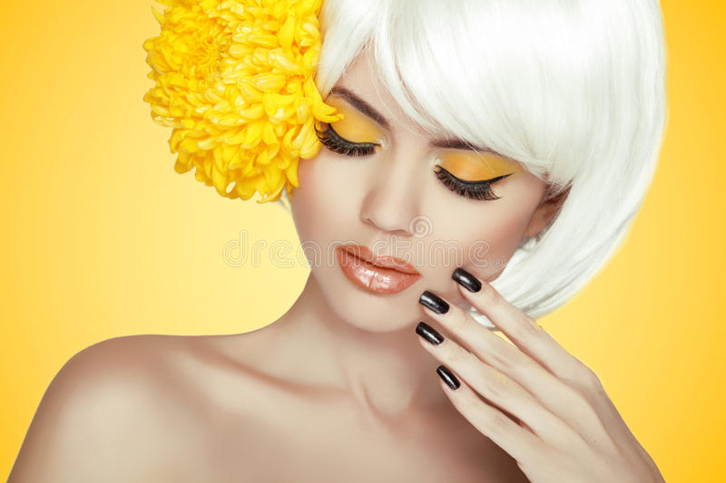 Beauty Portrait. Makeup. Manicured nails. Beautiful Spa Woman To. Uching her Face. Perfect Fresh Skin. Pure Beauty Model Girl. Isolated on yellow background royalty free stock image