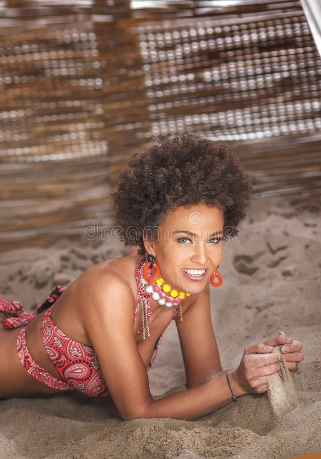 Beauty portrait of natural girl with afro lying on sand royalty free stock photos