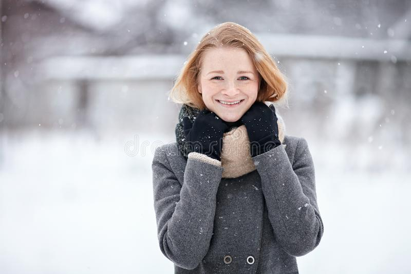 Beauty portrait natural looking young adorable redhead girl wearing knitted scarf grey coat on blurred winter background royalty free stock photography