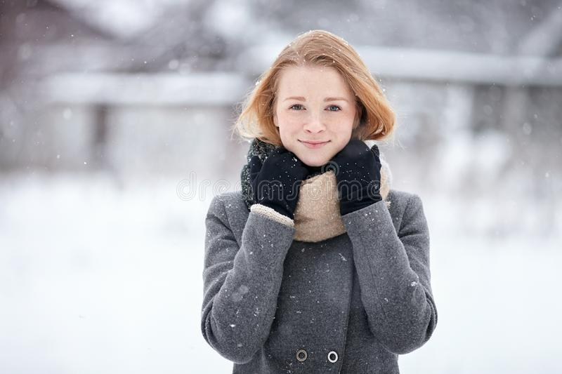 Beauty portrait natural looking young adorable redhead girl wearing knitted scarf grey coat on blurred winter background royalty free stock photos