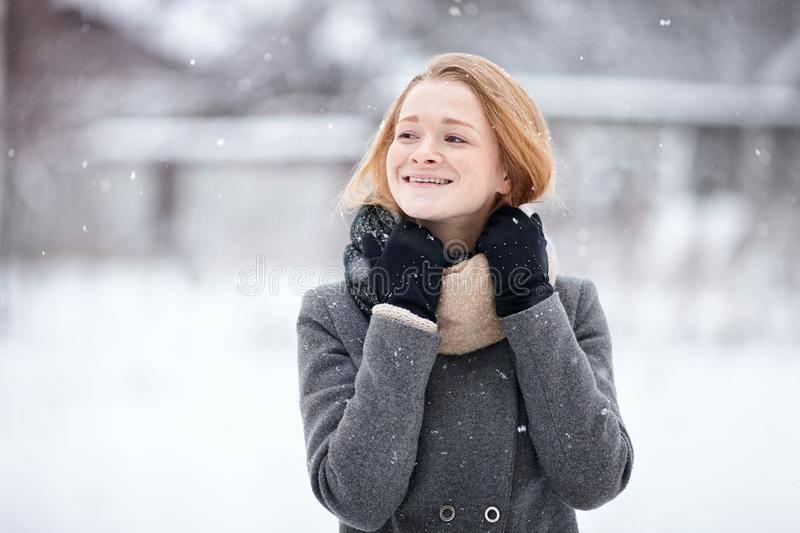 Beauty portrait natural looking young adorable redhead girl wearing knitted scarf grey coat on blurred winter background stock photo