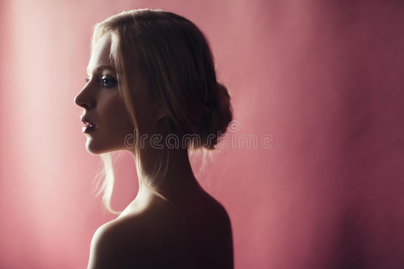 Beauty portrait of nordic natural blonde woman on pink background with copy space. Side view stock photography