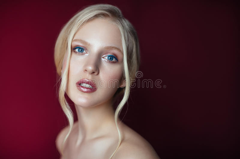 Beauty portrait of nordic natural blonde woman on red background. With copy space royalty free stock photo
