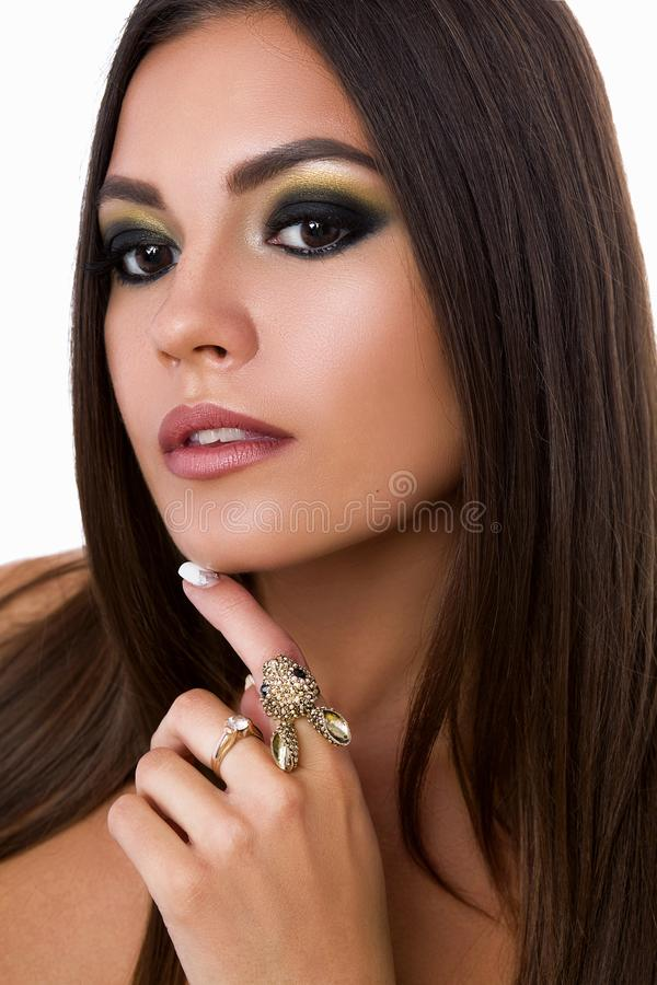 Beauty portrait of nude pretty brunette woman with long hair, evening make up, long eyelashes. Female touching face by. Hand with big ring and posing with royalty free stock photos