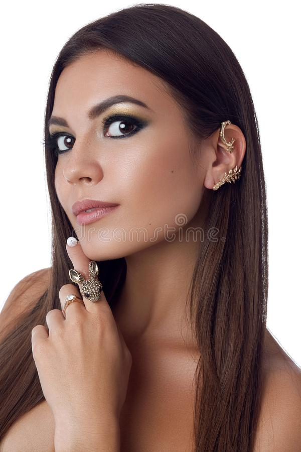 Beauty portrait of nude pretty brunette woman with long hair, evening make up, long eyelashes. Female touching face by. Hand with big ring and looking at camera royalty free stock images
