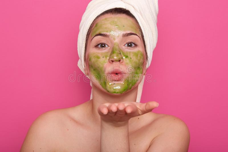 Beauty portrait of relaxed Caucasian woman in spa salon with green facial mask, wearing white towel isolated over rose background royalty free stock image