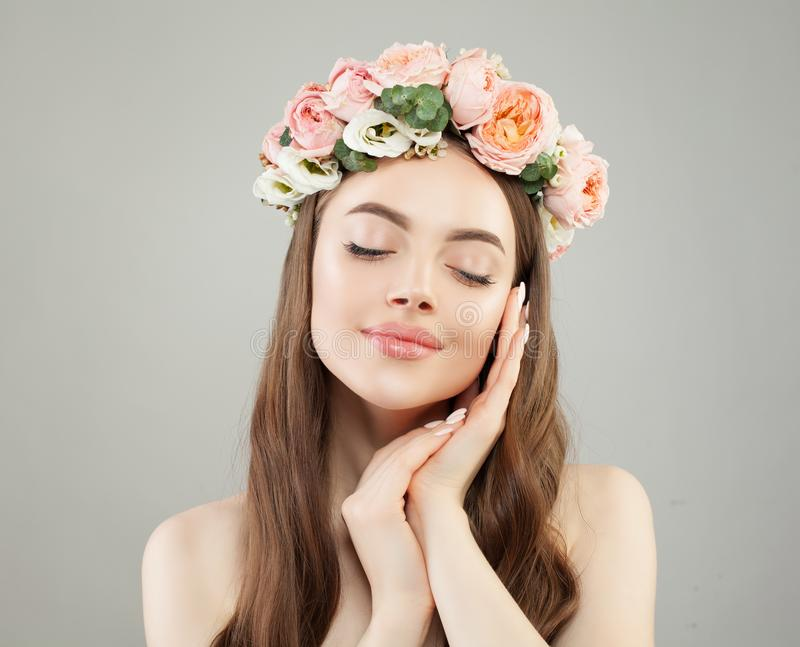 Beauty portrait of relaxing woman. Pretty model girl with clear skin, long shiny hair and flowers.  royalty free stock images