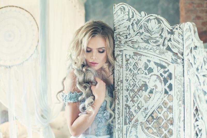 Beauty portrait of sensual woman in luxurious interior. Vintage romantic portrait of pretty blonde girl stock photography