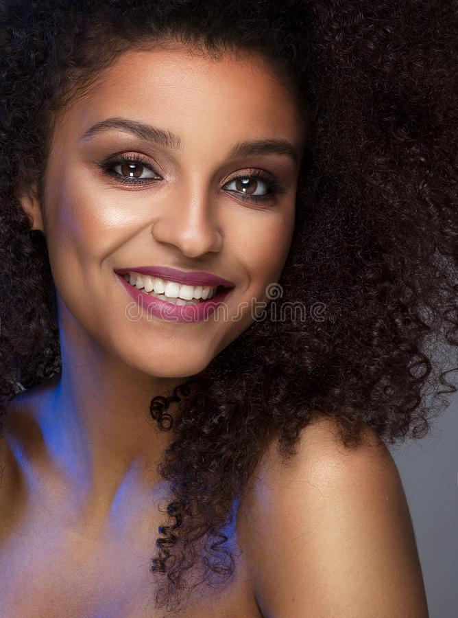 Beauty portrait of smiling dark skin young woman. Beauty portrait of smiling dark skin young woman with curly afro hair and glamour makeup. Studio shot on gray stock photos