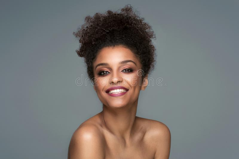 Beauty portrait of smiling dark skin young woman. Beauty portrait of smiling dark skin young woman with curly afro hair and glamour makeup. Studio shot on gray royalty free stock photos