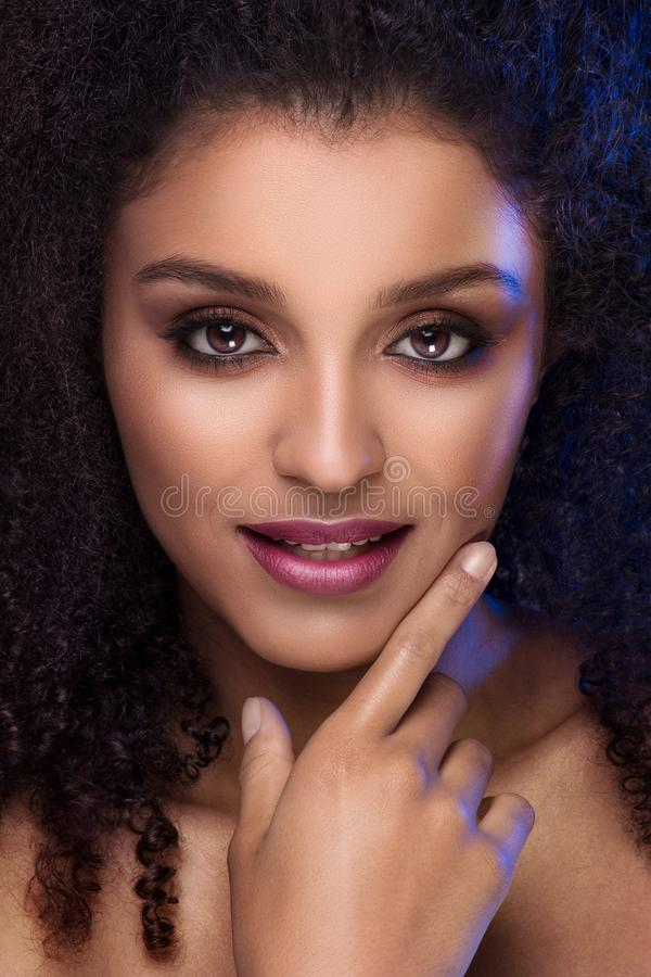 Beauty portrait of smiling dark skin young woman. Beauty portrait of smiling dark skin young woman with curly afro hair and glamour makeup. Studio shot royalty free stock photo
