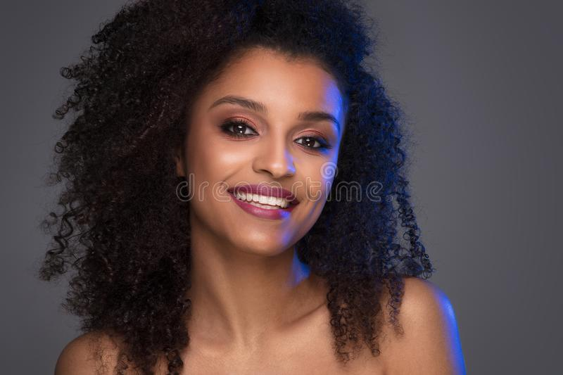 Beauty portrait of smiling dark skin young woman. With curly afro hair and glamour makeup. Studio shot on gray background, copy space royalty free stock photography