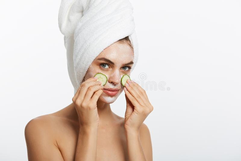 Beauty Portrait Of Smiling Woman With Towel On Head And Slice Of Cucumber In Hand Isolated On White Background. Beauty Portrait Of Smiling Woman With Towel On stock photos
