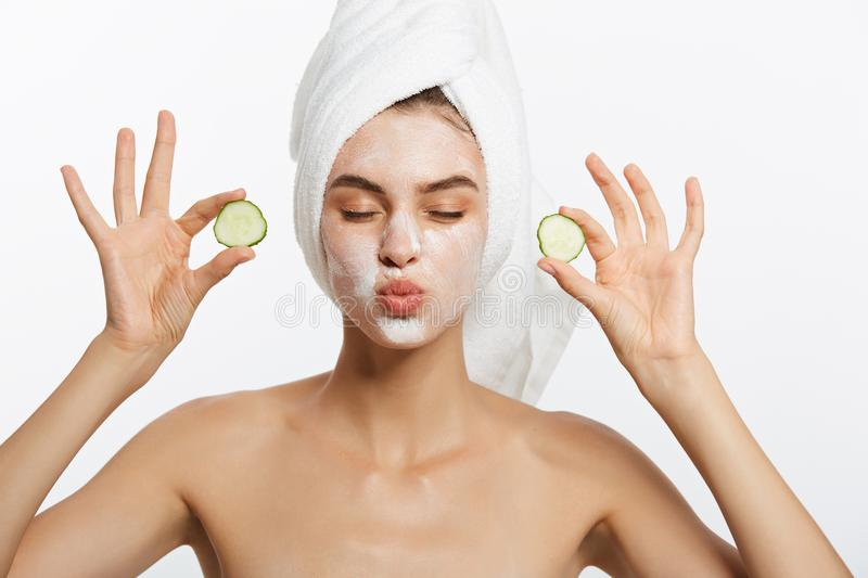 Beauty Portrait Of Smiling Woman With Towel On Head And Slice Of Cucumber In Hand Isolated On White Background. Beauty Portrait Of Smiling Woman With Towel On stock photography