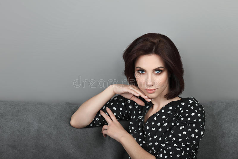 Beauty portrait sporty adult adorable fresh looking brunette woman gorgeous makeup bob hairdo posing grey sofa wall showing emotio. N and facial expression royalty free stock photos