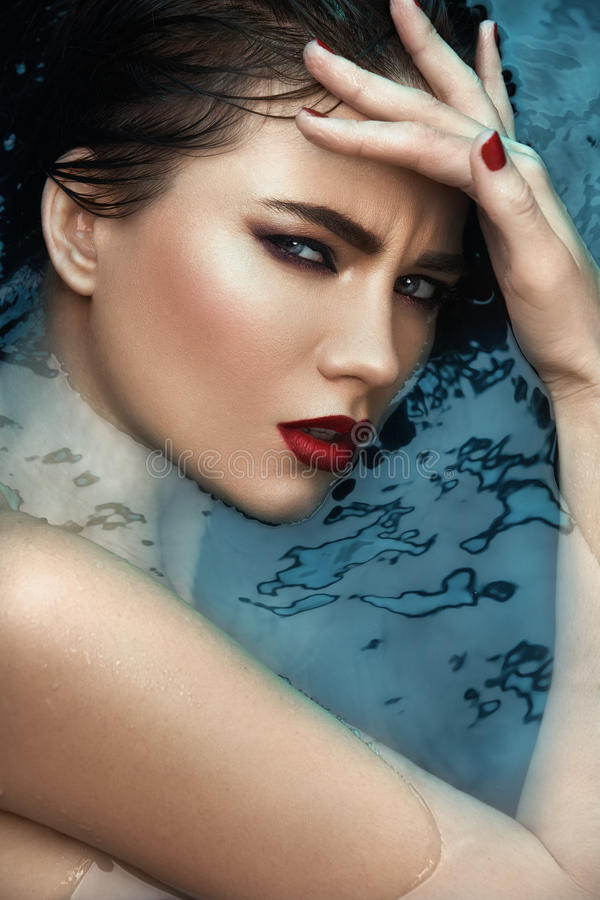 Beauty portrait in water, fashion vogue style shoot, close up makeup. royalty free stock photo