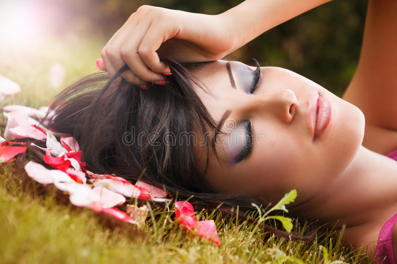 Beauty portrait of woman with flower petals near face stock image