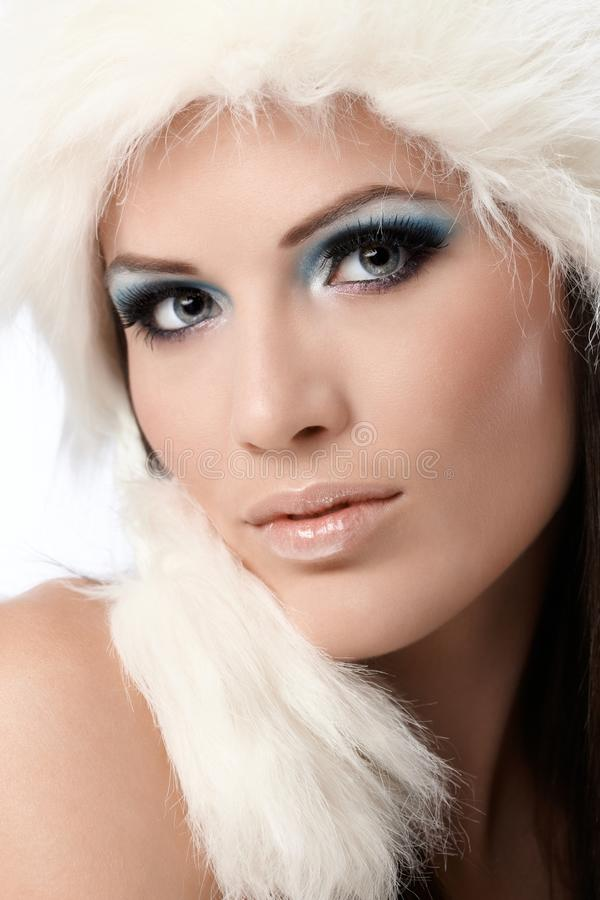 Beauty portrait of woman in fur cap and makeup. Beauty portrait of young woman in white fur cap and professional makeup royalty free stock image
