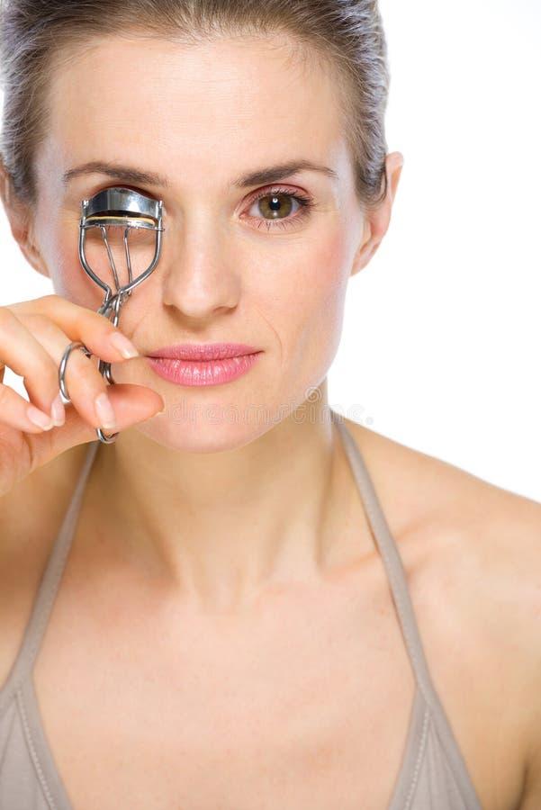 Beauty portrait of woman using eyelash curler stock image