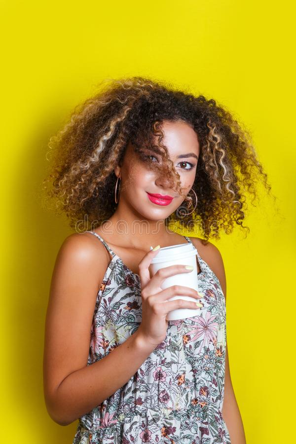 Beauty portrait of young african american girl with afro hairstyle. Girl posing on yellow background, looking at camera. stock images