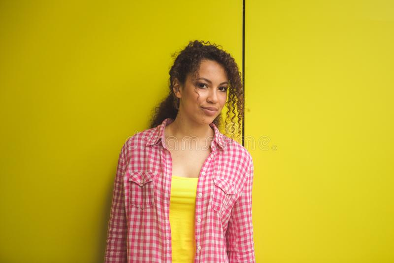Beauty portrait of young african american girl with afro hairstyle. Girl posing on yellow background, looking at camera royalty free stock photography