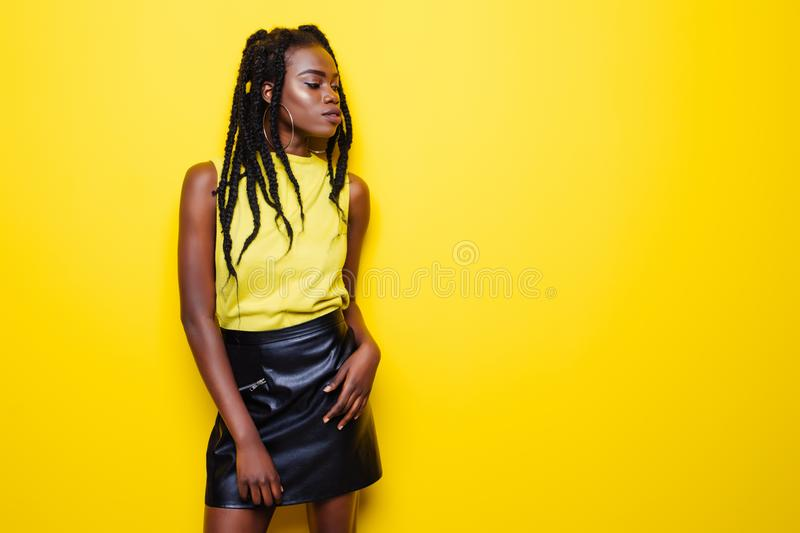 Beauty portrait of young african american girl with afro hairstyle. Girl posing on yellow background, looking at camera, smiling. stock photography