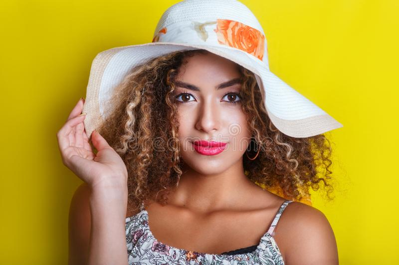 Beauty portrait of young african american girl with afro hairstyle in summer hat. Vacation concept. Beauty portrait of young african american girl with afro royalty free stock images