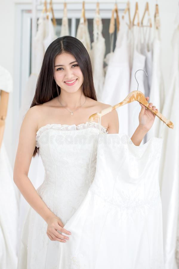 Beauty portrait of young asian bride choosing wedding dress in  wedding salon of  fashion store ,luxury stock photography