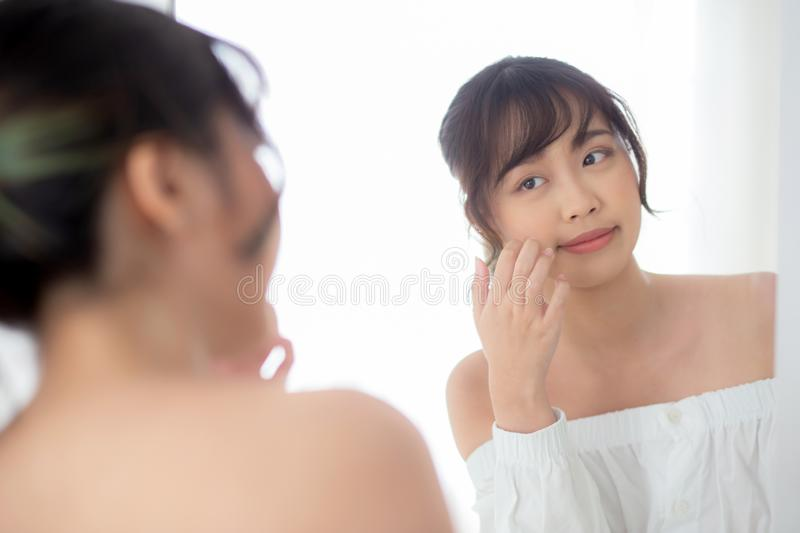 Beauty portrait young asian woman smiling look mirror of checking skin care caucasian with wellness in bedroom stock images